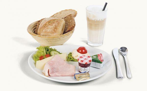 Klassisches Frühstück mit Wurst, Käse Marmelade, Kaffe und Brotkorb