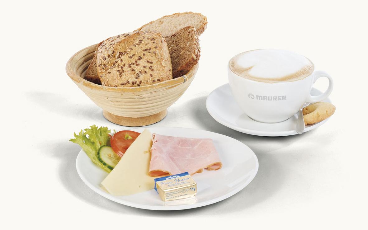 Kleines pikantes Frühstück mit Wurst, Käse, Kaffe und Brot