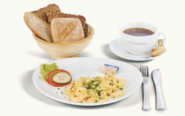 Rührei Natur mit einem Brotkorb und Tee