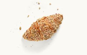 Ein Laugen-Croissant mit Saaten
